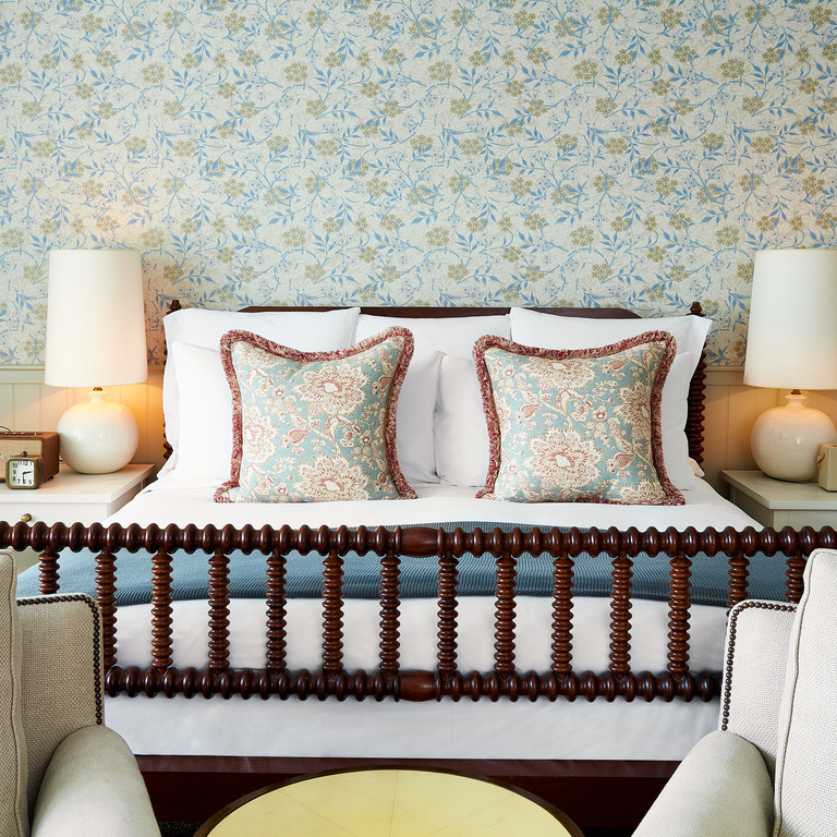 A room with a bed and vintage floral wallpaper