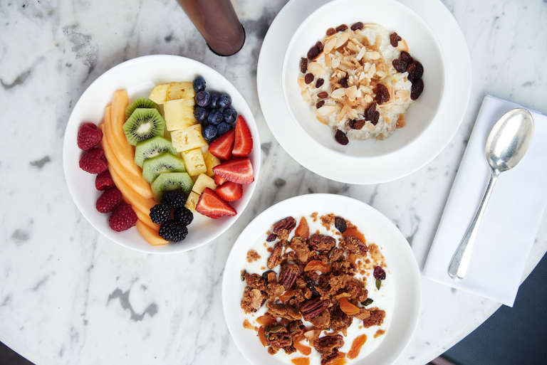 A fruit salad, a bowl of granola and Greek yoghurt