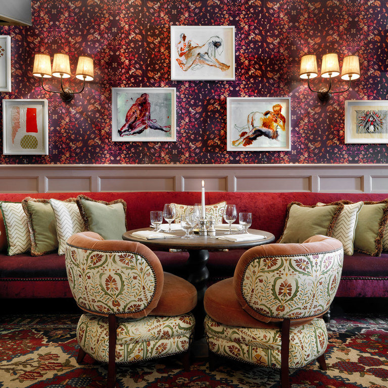 A dining room with artwork, bold wallpaper and vintage furnishings